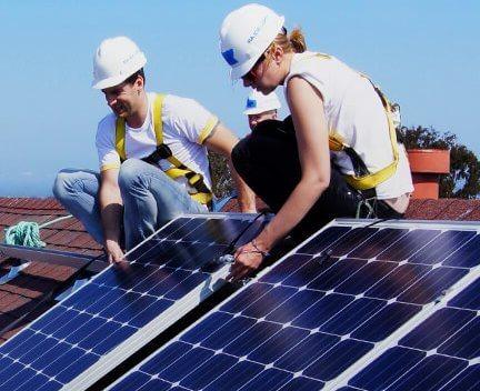 Сонячні панелі і монтажники на даху.